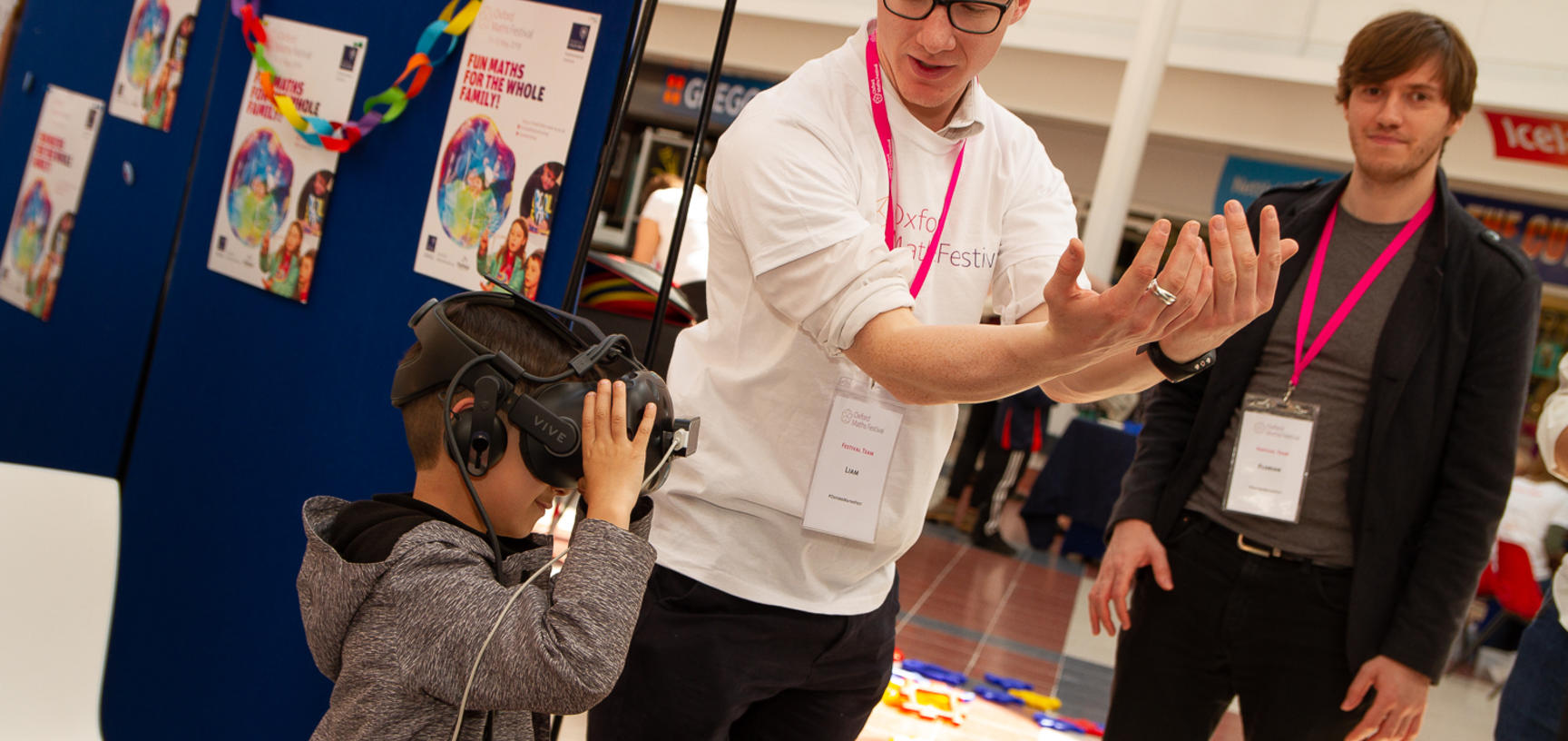 A young boy is shown how to use a VR headset at the Oxford Maths Festival