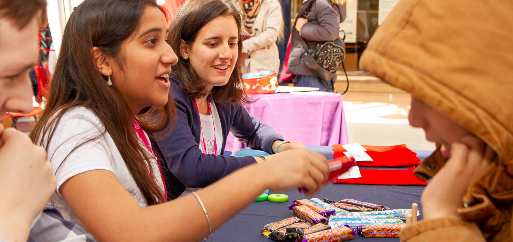 Volunteers play the chocolate game with children at the Oxford Maths Festival