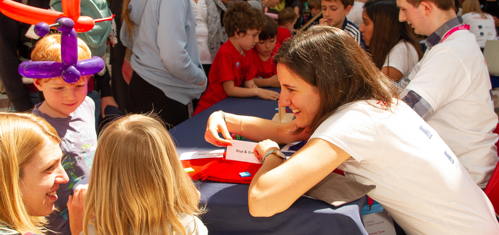 Children play a game with a volunteer at the Oxford Maths Festival