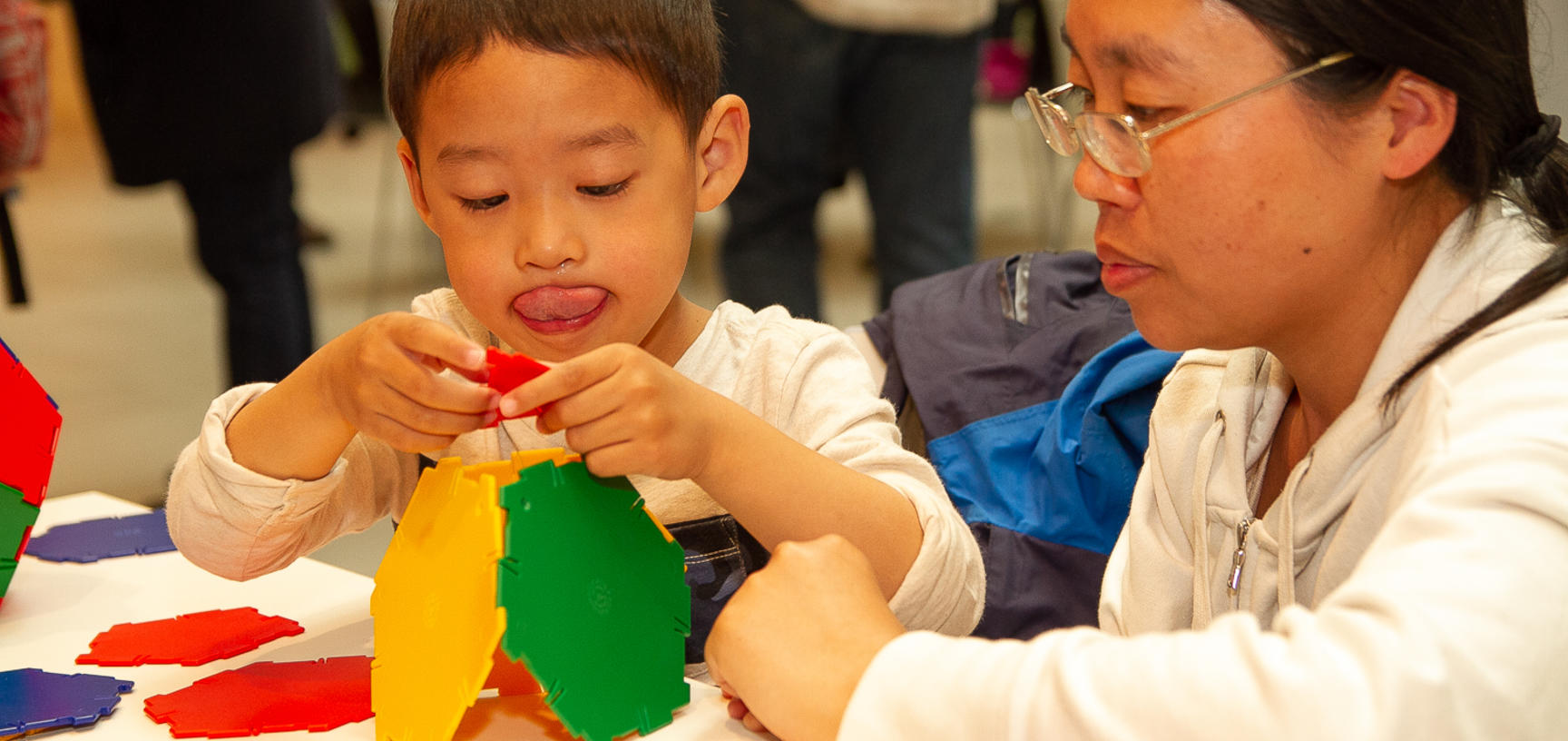 A young boy sticks his tongue out in concentration whilst playing with Polydron at the Oxford Maths Festival
