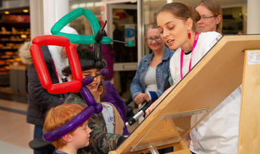 A volunteer shows children how a Galton board works at the Oxford Maths Festival.