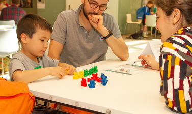 A family attempts a teddy bear puzzle at the Oxford Maths Festival
