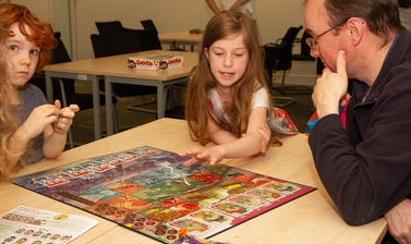 A family plays City of Zombies boardgame