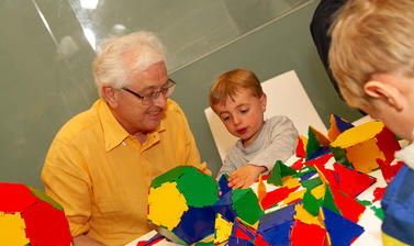 A child and carer play with Polydron
