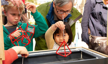 Visitors play with polyhedra shapes and bubble mixture