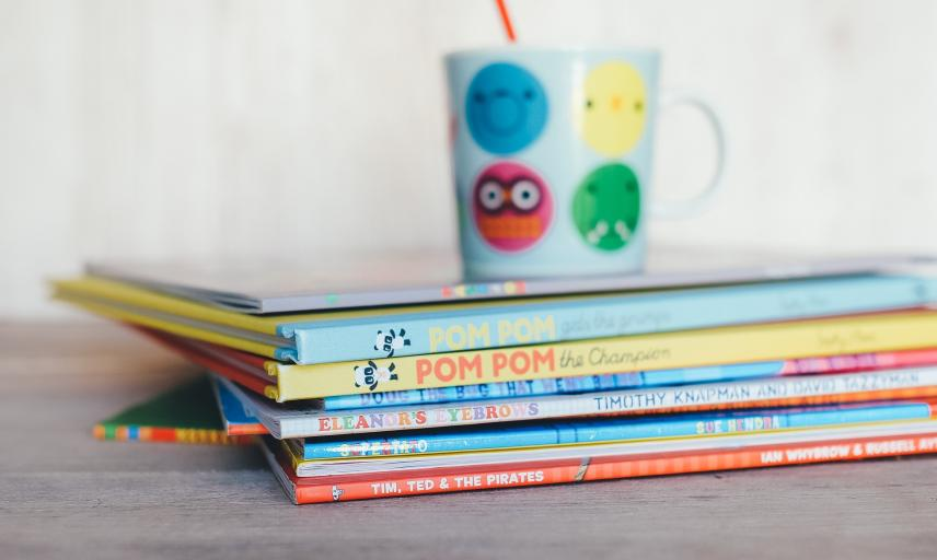 Childrens books piled with a mug on top