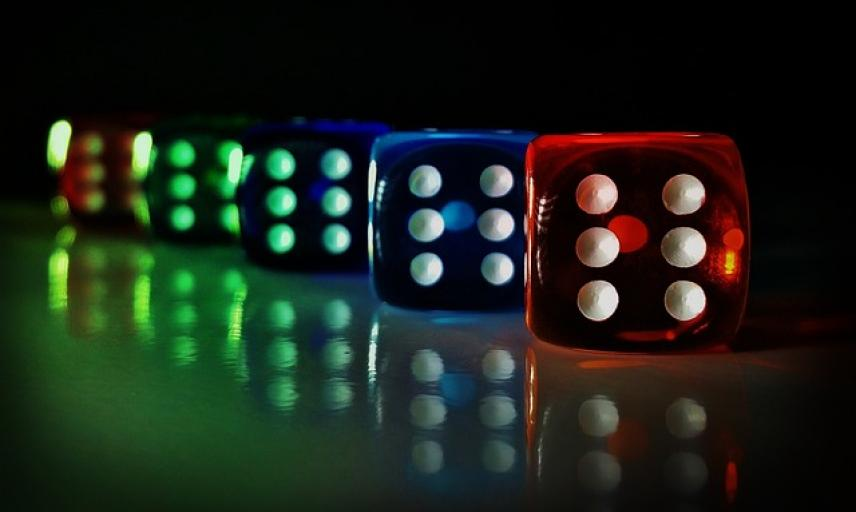 Colourful dice in a row on a dark background