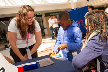 A volunteer watches as a young boy attempts the Tower of Hanoi at the Oxford Maths Festival