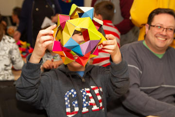 A child shows off their colourful origami creation
